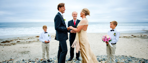 beach wedding couple standing with officiant